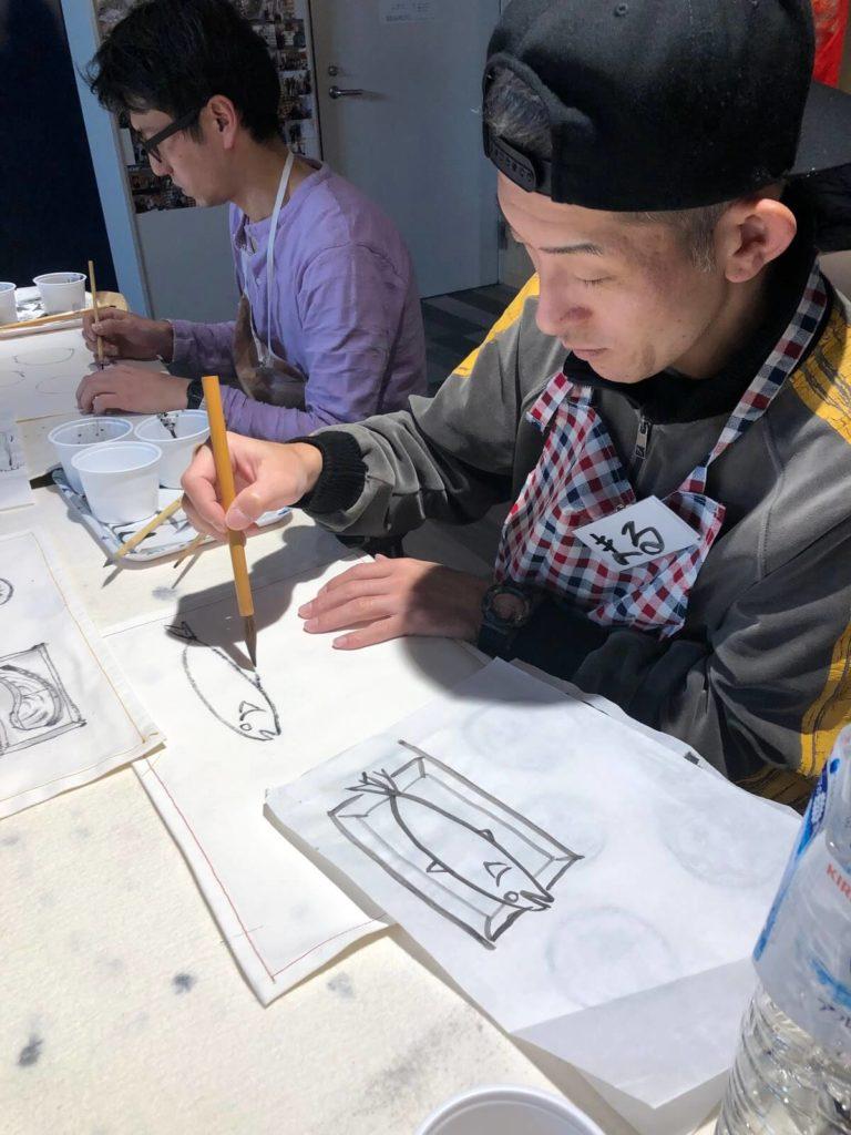 水墨画ワークショップで水墨画を描く男性